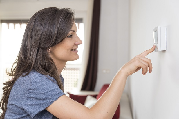 Woman programming a thermostat